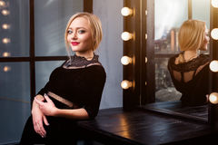 Atelieraufnahme des jungen und schönen Mädchens, das nahen Spiegel im schwarzen Kleid trägt im Studio steht Blondes Mädchen Stockfoto