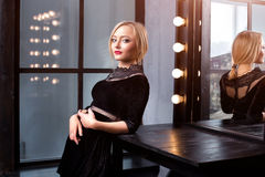 Atelieraufnahme des jungen und schönen Mädchens, das nahen Spiegel im schwarzen Kleid trägt im Studio steht Blondes Mädchen Lizenzfreie Stockbilder