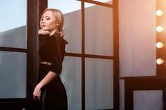 Atelieraufnahme des jungen und schönen Mädchens, das nahes Fenster im schwarzen Kleid trägt im Studio steht Blondes Mädchen Stockfotos