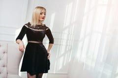 Atelieraufnahme des jungen und schönen Mädchens im schwarzen Kleid, das im Studio trägt Blondes Mädchen Lizenzfreie Stockfotos