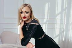 Atelieraufnahme des jungen und schönen Mädchens im schwarzen Kleid, das im Studio trägt Blondes Mädchen Stockfotografie