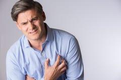 Atelieraufnahme des reifer Mann-leidenden Herzinfarkts Stockbild