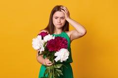 Atelieraufnahme des schönen brunette Mädchens hält großen Blumenstrauß von Burgunder-Pfingstrosen in der Hand, durchdachte Frau m stockbilder