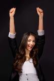 Atelieraufnahme einer attraktiven jungen Frau mit ihren Armen hob in Feier an Lizenzfreie Stockfotos