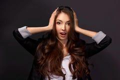 Atelieraufnahme einer attraktiven jungen Geschäftsfrau, die Überraschung schaut Lizenzfreies Stockbild
