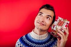 Atelieraufnahme eines jungen Mannes in der isländischen Strickjacke, die eine Geschenkbox hält Weihnachts- oder Feierkonzept des  stockfotografie