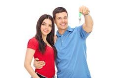Atelieraufnahme eines jungen Paares, das mit einem Schlüssel aufwirft Stockbild
