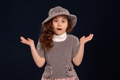Atelieraufnahme eines reizenden Kleinkindes mit einem langen, gelockten Haar, das auf einem schwarzen Hintergrund aufwirft lizenzfreies stockfoto