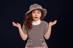 Atelieraufnahme eines reizenden Kleinkindes mit einem langen, gelockten Haar, das auf einem schwarzen Hintergrund aufwirft stockfoto