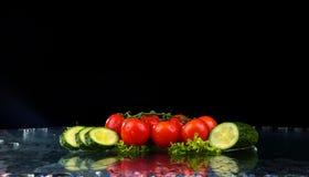 Atelieraufnahme mit Frostbewegung von Kirschtomaten und Scheiben der Gurke im Wasser spritzen auf schwarzem Hintergrund Lizenzfreies Stockbild