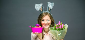 Atelieraufnahme Ohren und von Halten eines von glücklichen tragenden Häschens der jungen Frau eines bunten Ostereies lizenzfreie stockfotografie
