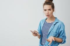 Atelieraufnahme störte den gestörten ärgerlichen jungen weiblichen modernen Unternehmer, der die Geschäftsanrufe macht, die g lizenzfreie stockfotografie