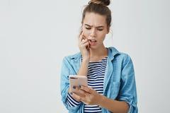 Atelieraufnahme verdutzte die gestörte nette junge Frau 25s, die online Rechnungsliste, die Stirn runzelndes gestörtes beißendes  stockfotos