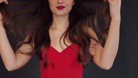 Atelieraufnahme von Brunette mit den roten Lippen, die mit dem Haar spielen stock video