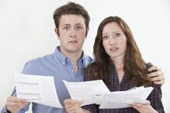 Atelieraufnahme von den besorgten Paaren, die Rechnungen betrachten Stockbilder