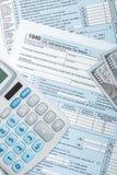 Atelieraufnahme von Steuerformular der Vereinigten Staaten von Amerika 1040 mit Taschenrechner und VON US-Dollars über ihr Lizenzfreie Stockbilder
