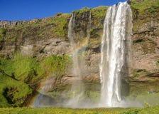Atemberaubend schöner Wasserfall Seljalandsfoss am sonnigen Sommertag mit Regenbogen Süd-Island, Europa stockfotografie