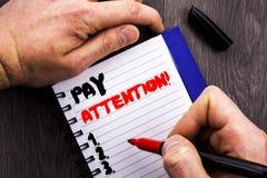 Atenção escrita à mão do pagamento da exibição do sinal do texto A foto conceptual seja cuidadosa é cuidadoso o alarme consciente imagem de stock