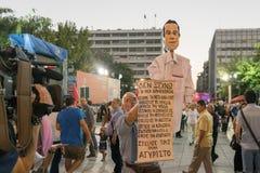 Atenas, Grécia 18 de setembro de 2015 Protestante com uma caricatura de Alexis Tsipras que dá uma entrevista a um canal local Imagem de Stock