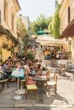 Atenas, Grécia 13 de setembro de 2015 Turistas e povos locais no café bebendo e em apreciar da rua famosa de Plaka seu tempo livr Fotografia de Stock