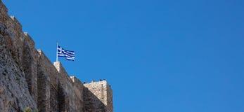 Atenas, Grécia, rocha da acrópole, bandeira grega que acena no céu azul claro, bandeira fotografia de stock