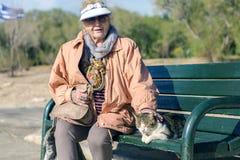 Atenas, Grecia - 16 de diciembre 2018 una mujer mayor y un gato sin hogar foto de archivo libre de regalías