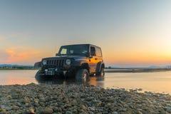 Atenas, Grecia 1 de julio de 2016 Jeep 4x4 contra la puesta del sol El jeep consiguió pegado en el fango Imágenes de archivo libres de regalías