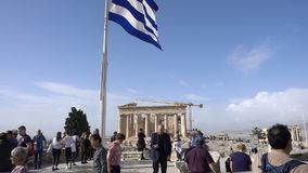 Atenas, Grecia - 15 de noviembre de 2017: turistas y bandera griega gigantesca en la acrópolis ateniense almacen de video