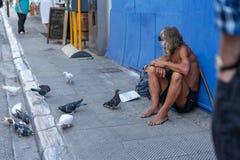 ATENAS, GRECIA - 16 DE SEPTIEMBRE DE 2018: Hombre sin hogar que se sienta en las calles de Atenas imagen de archivo