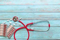 Atención sanitaria del día de salud de mundo y estetoscopio rojo y medicina del concepto médico en el fondo de madera azul Foto de archivo