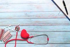 Atención sanitaria del día de salud de mundo y estetoscopio rojo y medicina del concepto médico en el fondo de madera azul Fotografía de archivo