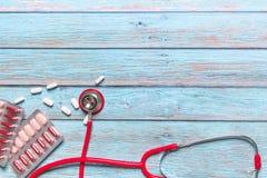 Atención sanitaria del día de salud de mundo y estetoscopio rojo y medicina del concepto médico en el fondo de madera azul Imagen de archivo