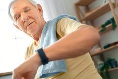 Atención sanitaria del ejercicio del hombre mayor en casa que comprueba el tiempo serio Fotos de archivo libres de regalías