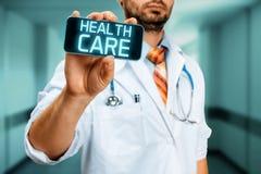 Atención sanitaria del seguro del doctor With Smartphone With Imagenes de archivo