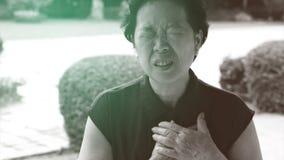 Atención sanitaria mayor asiática del movimiento del ataque del corazón al dolor de pecho de la mujer imagenes de archivo