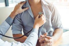 Atención sanitaria paciente arterial del hombre de la presión arterial del doctor Measuring en hospital foto de archivo