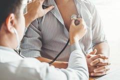 Atención sanitaria paciente arterial del hombre de la presión arterial del doctor Measuring en hospital foto de archivo libre de regalías