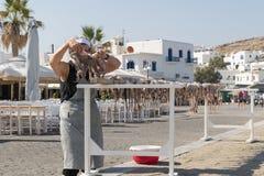 Atene, Grecia 15 agosto 2015 Signora anziana all'isola di Paros che appende un polipo fuori di una locanda per asciugarsi al sole Immagini Stock Libere da Diritti