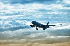 Aterragem do avião de passageiros no céu da noite Fotos de Stock