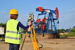 Aterrice al experto del topógrafo en el trabajo sobre un pozo de petróleo imagenes de archivo