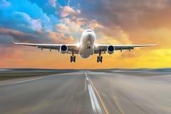 Aterrissagem da chegada do voo do avião em uma pista de decolagem na noite durante um por do sol vermelho brilhante foto de stock royalty free