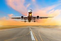 Aterrissagem da chegada do voo do avião em uma pista de decolagem na noite durante um por do sol vermelho brilhante fotos de stock