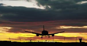 Aterrissagem da silhueta do avião do jato no céu nebuloso ilustração stock