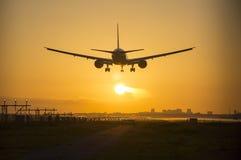 Aterrissagem de avião durante o crepúsculo Fotografia de Stock