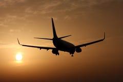 Aterrissagem de avião no por do sol imagens de stock royalty free