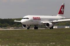 Aterrissagem de aviões internacional suíça de Airbus A320-214 das linhas aéreas na pista de decolagem Imagem de Stock Royalty Free