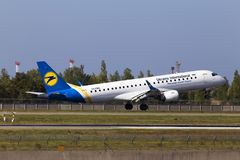 Aterrissagem de aviões de Ukraine International Airlines Embraer ERJ190-100 na pista de decolagem Fotografia de Stock