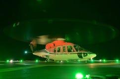 A aterrissagem de noite do helicóptero na plataforma petrolífera a pouca distância do mar Imagem de Stock