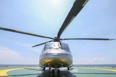 Aterrissagem do estacionamento do helicóptero na plataforma a pouca distância do mar Grupos ou passageiro de transferência do hel Imagens de Stock