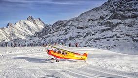 Aterrizaje de aeroplano amarillo al centro turístico alpino en las montañas suizas en winte Fotos de archivo